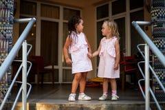 Les bébés de blonde et de brune de deux soeurs dans la même chose s'habille, tenant des mains Image libre de droits