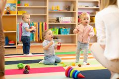 Les bébés de crèche jouent sur le plancher avec des soignants ou les mères au centre de soins de jour image stock