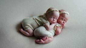 Les bébés jumeaux dorment dans la huche dans des robes Image stock