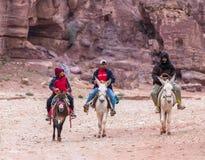 Les bédouins sur des ânes montent au pied de la roche rouge dans PETRA près de la ville de Wadi Musa en Jordanie images stock