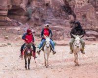 Les bédouins sur des ânes montent au pied de la roche rouge dans PETRA près de la ville de Wadi Musa en Jordanie photo libre de droits