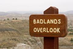 Les bad-lands donnent sur le signe en bois Images stock