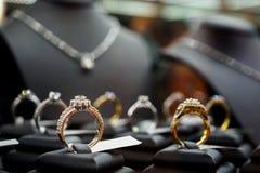 Les bagues à diamant et les colliers de bijoux montrent dans le magasin de détail de luxe images libres de droits