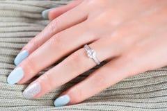 Les bagues de fiançailles de mariage de diamants sur le doigt femelle avec les ongles bleus manicure photographie stock