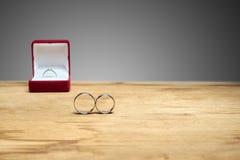 Les bagues de fiançailles sont sur la table, et l'engagement arrière Photos libres de droits