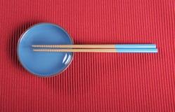 Les baguettes et la cuvette bleues d'Aqua sur le tapis d'endroit rouge ajournent l'arrangement Photo stock
