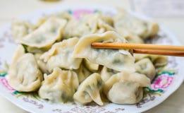Les baguettes prennent des boulettes de Boilded Chineses d'un plat photos libres de droits