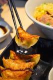 Les baguettes sélectionnent le style japonais Fried Gyoza Dumplings d'un plat noir images libres de droits