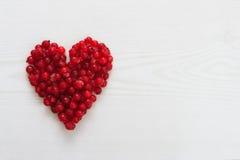Les baies actuelles rouges au coeur forment sur le conseil en bois Photos stock