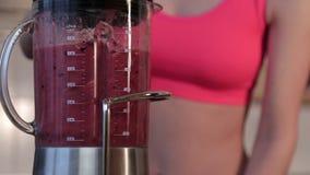 Les baies, les bananes et l'amande de mélange de femme traient pour faire un smoothie vert sain banque de vidéos