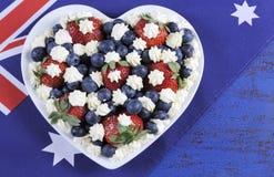 Les baies rouges, blanches et bleues de thème avec la crème fouettée fraîche se tient le premier rôle avec le drapeau australien Photographie stock libre de droits
