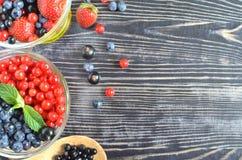 Les baies sont rouges et bleues dans un bol en verre sur un fond en bois noir photo stock