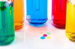 Les baisses colorées et les bouteilles en verre transparentes remplies ont coloré le liquide avec le compte-gouttes Photo libre de droits