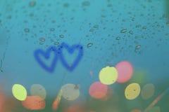 Les baisses de pluie et deux coeurs écrivent sur la fenêtre avec le bokeh léger Photos stock