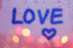 Les baisses de pluie et l'amour de mot écrivent sur la fenêtre avec le bokeh léger Photos libres de droits
