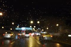 Les baisses de pluie sur la fenêtre avec la rue brouillent des lumières Photographie stock libre de droits