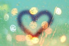 Les baisses et le coeur de pluie écrivent sur la fenêtre avec le bokeh léger Images stock