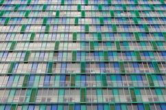 Les balcons et les fenêtres d'un bâtiment, maisons de rapport ont donné aux trellis une consistance rugueuse verts beiges photographie stock libre de droits