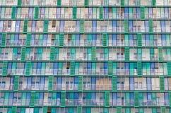 Les balcons et les fenêtres d'un bâtiment, maisons de rapport ont donné aux trellis une consistance rugueuse verts beiges images stock