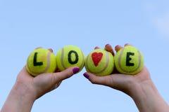 Les balles de tennis aiment le mot et le coeur - tenus dans des mains par la femme Images libres de droits