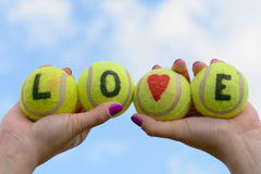 Les balles de tennis aiment le mot et le coeur - tenus par la femme Photos libres de droits