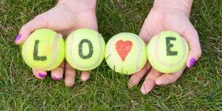 Les balles de tennis avec l'amour de mot et le coeur d'amour se sont tenues par la femme Image stock