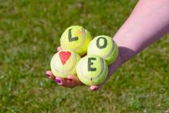 Les balles de tennis avec l'amour de mot et le coeur d'amour se sont tenues par la femme Photos stock