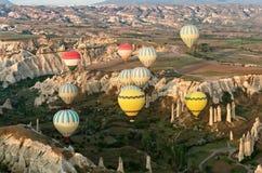 Les ballons à air chauds au-dessus de la montagne aménagent en parc dans Cappadocia photographie stock libre de droits