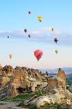 Les ballons à air chauds au-dessus de la montagne aménagent en parc dans Cappadocia photos libres de droits