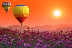 Les ballons à air chauds au-dessus du cosmos fleurissent au coucher du soleil avec la fusée images stock