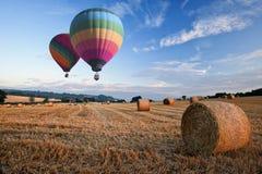 Les ballons à air chauds au-dessus du coucher du soleil de balles de foin aménagent en parc Image stock