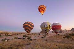 Les ballons à air chauds colorés volant au-dessus de la roche aménagent en parc Images libres de droits