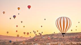 Les ballons à air chauds colorés volant au-dessus de la roche aménagent en parc chez Cappadoc images libres de droits
