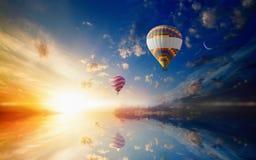Les ballons à air chauds vole en ciel de coucher du soleil Photos stock
