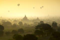 Les ballons à air chauds volent au-dessus du champ de ville antique de pagoda sur la scène de lever de soleil de silhouette chez  Photo libre de droits