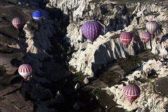 Les ballons à air chauds volent au-dessus du paysage spectaculaire de Goreme dans la région de Cappadocia de la Turquie Photos libres de droits