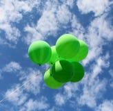 Les ballons verts volent loin dans le ciel photographie stock libre de droits