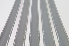 Les bandes exposées déroulées de film de 35mm au-dessus d'un fond blanc Photographie stock