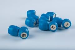 Les barillets en plastique bleus pour le jeu de loto avec des nombres s'étendent sur le fond blanc Photographie stock
