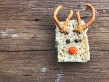 Les barres carrées faites maison du riz croustillantes décorent le renne de Noël sur la table en bois image stock