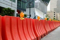 Les barrières en plastique oranges de débardeur protègent un chantier de construction images libres de droits