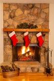 Les bas de Noël ornent une belle cheminée en pierre avec un feu rougeoyant photo stock