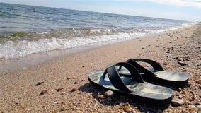 Les bascules se tiennent sur le bord de la mer, bascules noires sur la plage banque de vidéos