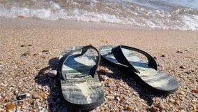 Les bascules se tiennent sur le bord de la mer, bascules sur la plage dans la perspective du mouvement lent de mer clips vidéos
