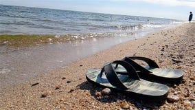 Les bascules se tiennent sur le bord de la mer, bascules sur la plage dans la perspective du mouvement lent de mer banque de vidéos