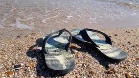 Les bascules se tiennent sur le bord de la mer, bascules sur la plage dans la perspective du mouvement lent de mer, secousse noir clips vidéos