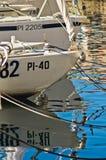 Les bateaux blancs et la réflexion de ciel bleu chez Piran hébergent, Istria Image stock