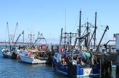 Les bateaux de pêche amarrés au dock avec un camion de collecte avec la porte s'ouvrent et le rivage opposé évident à travers la  photographie stock