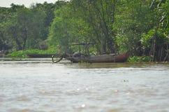 Les bateaux de pêche en bois vietnamiens ont amarré dans la jungle par une rivière boueuse Photographie stock