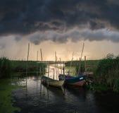 Les bateaux de pêche ont amarré au petit pont en bois au-dessus de la rivière Photos stock